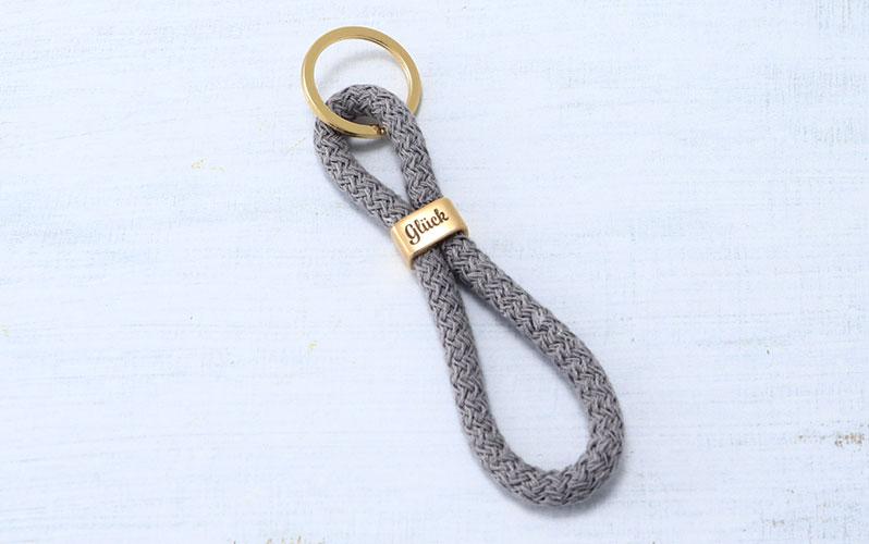 """Schlüsselanhänger mit Segeltau und Gravur """"Glück"""" grau"""