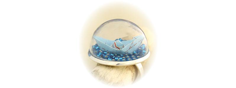 Maritimer Ring mit Papierboot unter Glaskuppel